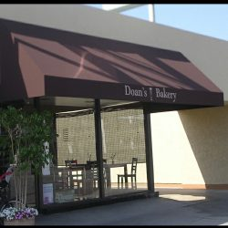 Custom storefront awning for Doan's Bakery with brown awning fabric