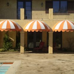 Residential dome awnings with striped orange and white awning fabric
