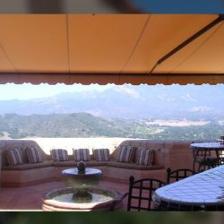 Dark orange awning fabric on a residential retractable awning with a great view