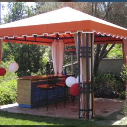 Residential cabana with orange awning fabric and custom drapes