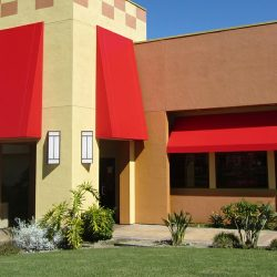 Custom commercial storefront awning with red awning fabric
