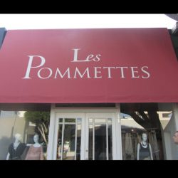 White awning graphics on a red storefront awning for Les Pommettes
