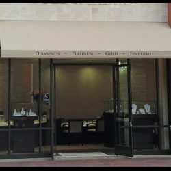 Black awning graphics on a tan storefront awning