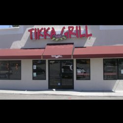 Red storefront awning with white awning graphics for Tikka Grill