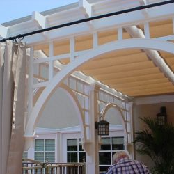 White trellis cover with tan slide wire awning and custom drapes