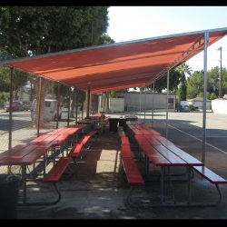 Metal tension shade with red awning fabric for a basketball court