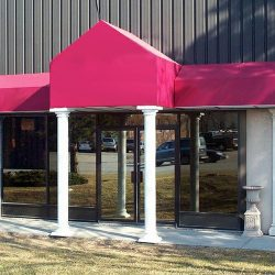 Custom storefront awning with white columns and red awning fabric