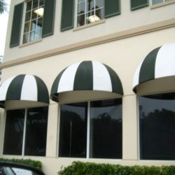 Window dome awnings with white and green awning fabric