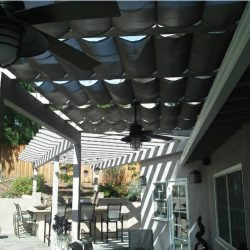 Residential trellis cover with dark retractable awning fabric
