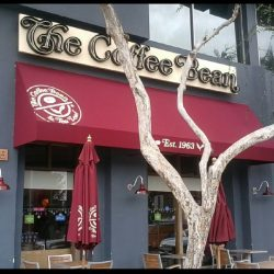 Red storefront awning with awning graphics for The Coffee Bean