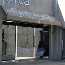 Tan storefront awning with white awning graphics