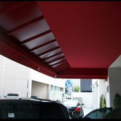 Custom carport awning with red awning fabric and metal