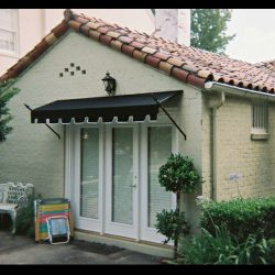 Residential doorway spearhead awning with black awning fabric
