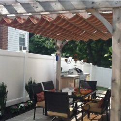Red and gold retractable awning fabric on a wood trellis cover