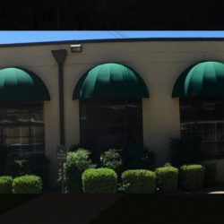 Window dome awnings with green awning fabric