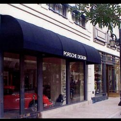 Navy blue storefront awning with white awning graphics for Porsche Design
