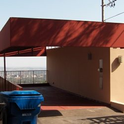 Custom carport awning with rusty red awning fabric and metal