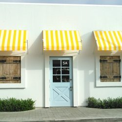 Commercial spearhead awnings with striped yellow and white awning fabric