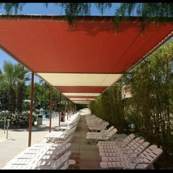 Custom tension shade with red and white awning fabric for a pool area