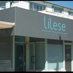 Custom storefront awning for Lilese with grey awning fabric and custom awning graphics