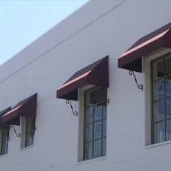 Residential window awnings with dark red awning fabric