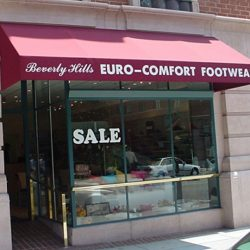 Red storefront awning with white awning graphics for Euro-Comfort Footwear