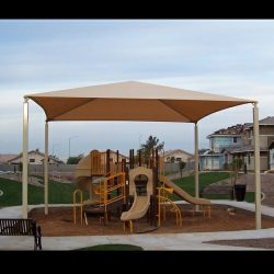 Tension shade with tan awning fabric for a residential playground area