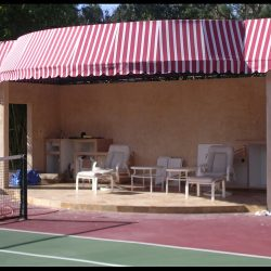 Custom awning with red and white striped awning fabric for a tennis court