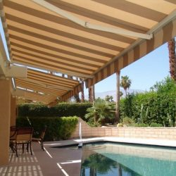 Retractable awning with striped awning fabric for a pool area