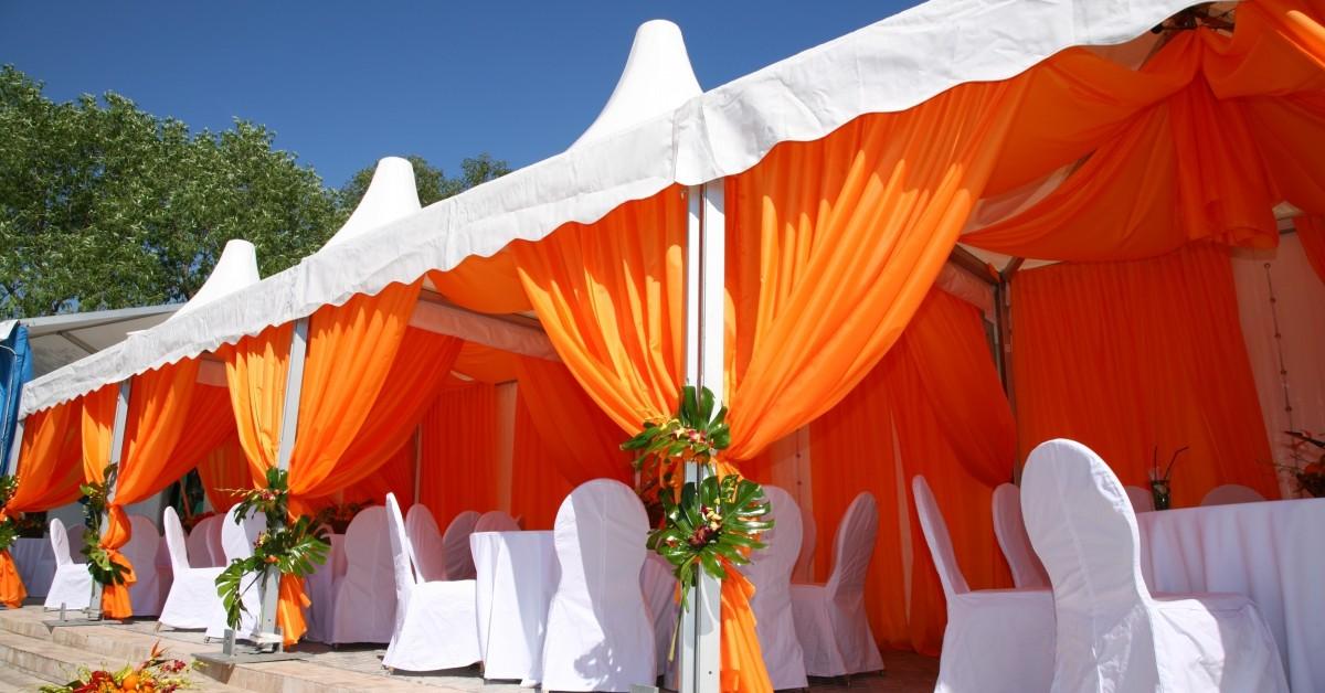 Custom cabana with orange outdoor drapes and white awning fabric