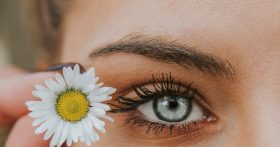 Woman holding flower next to eye, prominently featuring sculpted a eyebrow