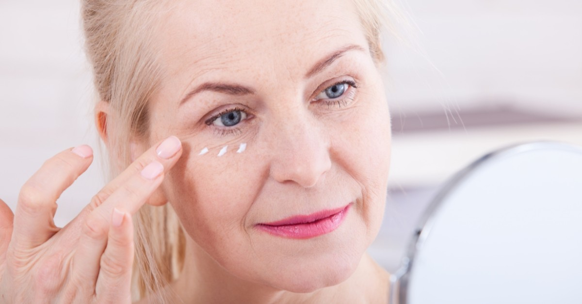 Middle-aged woman looking in the mirror and applying cream underneath her right eye.