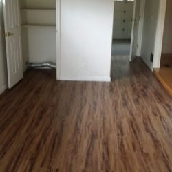 Wood laminate flooring installation with closet and hallway view