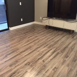 Freshly installed wood laminate flooring in entertainment room