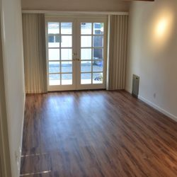 New wood laminate flooring installation in empty room