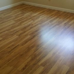 Smooth wood laminate floor installation with reflection