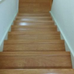 Oak colored wood laminate flooring facing down stairs