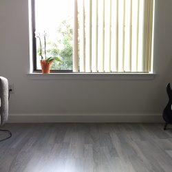 Grey wood laminate flooring in entertainment room with window