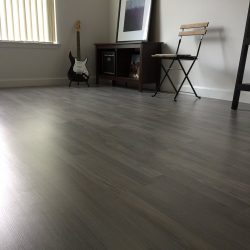 Closeup of grey wood laminate flooring in entertainment room