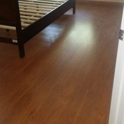 Oak colored laminate wood flooring installation in bedroom