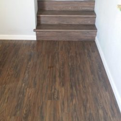 Dark brown wood laminate flooring freshly installed on stairs and in bedrooms