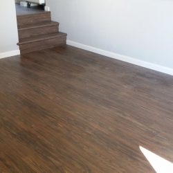 Dark wood laminate flooring installation including stairs