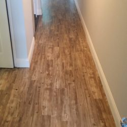 Warm brown laminate wood flooring installed in hallway