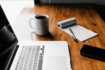 image of laptop, coffee mug, note pad and pen, and smartphone sitting on a wooden table