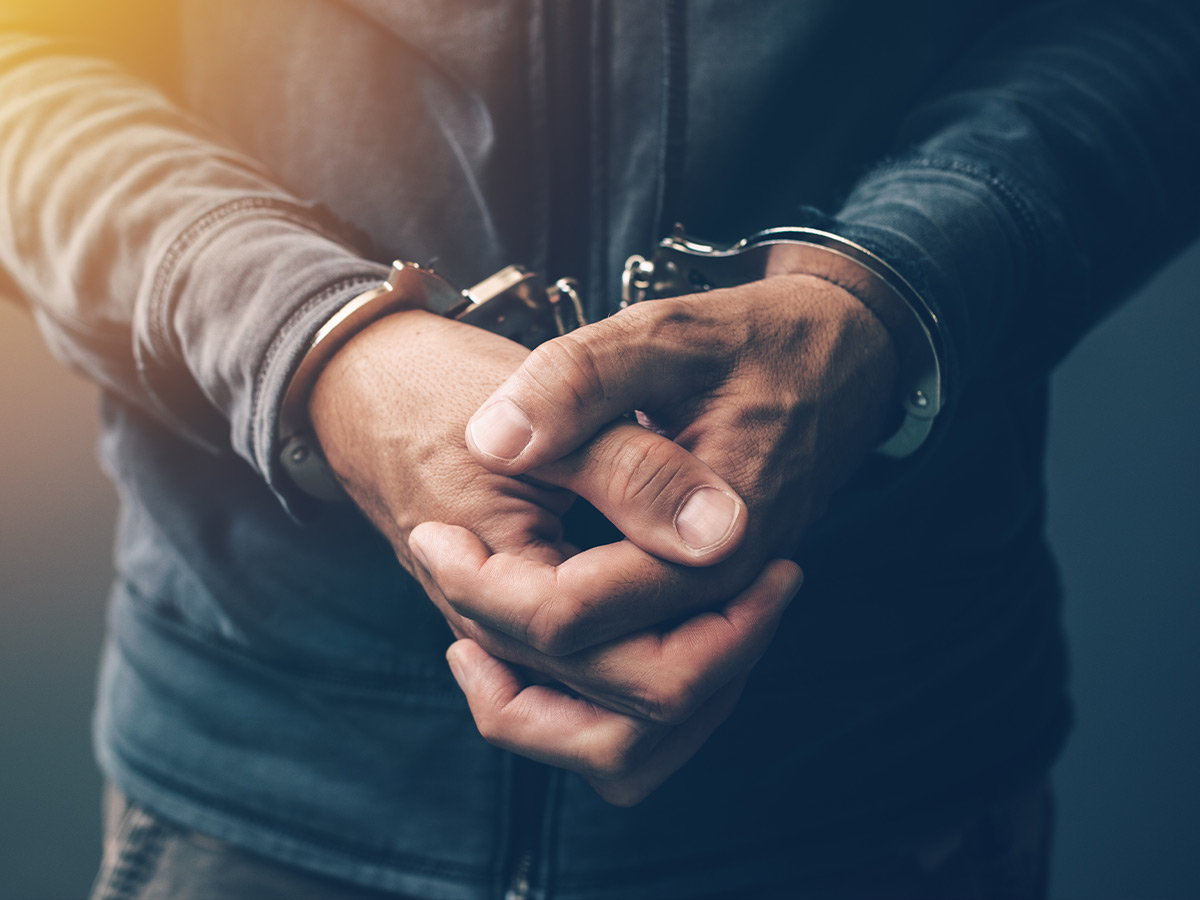 Close-up of man's hands with handcuffs.