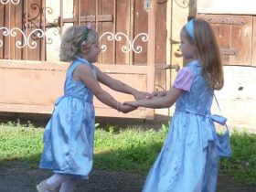Two young girls in blue dresses dancing together at Watch Me Grow Las Vegas