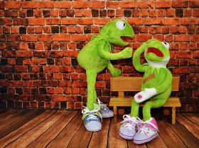 Two Kermit The Frog puppets, one wearing bandaids and bandage