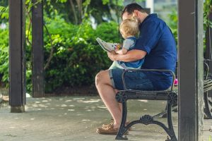 man reading to his child