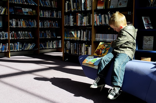 little bot reading in a library