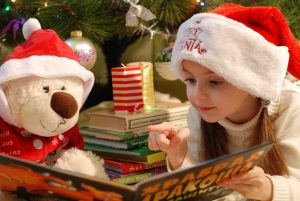 little girl reading a Christmas book